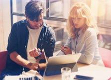 研究便携式计算机的两个年轻工友在晴朗的办公室 拿着纸张文件和指向在笔记本的妇女 免版税库存图片