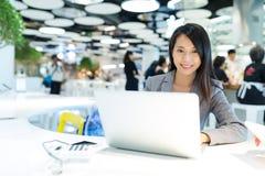 研究便携式计算机的女商人在共同工作的地方 库存照片