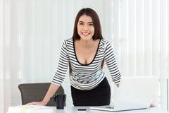 研究便携式计算机的女商人在办公室 免版税库存图片