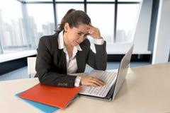 研究便携式计算机的女实业家佩带的西装在现代办公室室 免版税图库摄影