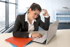 研究便携式计算机的女实业家佩带的西装在现代办公室室 免版税库存照片