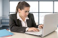 研究便携式计算机的女实业家佩带的西装在现代办公室室 库存照片