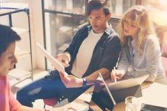 研究便携式计算机的小组三个年轻工友在晴朗的办公室 指向的妇女拿着纸张文件和  库存照片