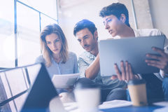 研究便携式计算机的小组三个年轻工友在办公室 拿着片剂和指向在触摸屏上的妇女 免版税库存照片