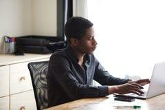 研究便携式计算机的年轻非裔美国人的商人在办公室 库存照片