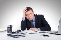 研究便携式计算机的沮丧的年轻商人在offi 免版税库存图片