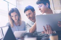 研究便携式计算机的特写镜头观点的三个年轻工友在办公室 拿着片剂和指向在接触的妇女 库存照片