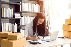 研究便携式计算机的美丽的亚裔少妇 免版税图库摄影