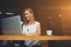 研究便携式计算机的美丽的愉快的妇女在咖啡馆酒吧的咖啡休息期间 库存图片