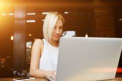 研究便携式计算机的美丽的白肤金发的女学生在她的演讲前在大学 库存图片