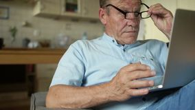 研究便携式计算机的老人坐在他的厨房里 网路银行,填好纳税申报,网上购物 股票视频