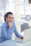 研究便携式计算机的聪明的女实业家 免版税库存照片