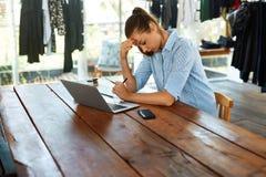 研究便携式计算机的被注重的女商人 头疼痛苦 图库摄影