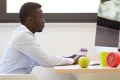 研究便携式计算机的年轻非裔美国人的商人 免版税库存图片