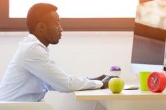 研究便携式计算机的年轻非裔美国人的商人 库存照片