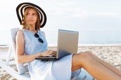研究假期的自由职业者女孩,在美丽的海前面,与膝上型计算机坐海洋 免版税图库摄影