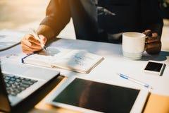 研究分析与文件图表的苦读者的项目的商人公司财政报告平衡在现代办公室空间 库存图片