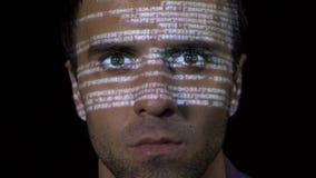 研究反病毒程序的一个年轻IT程序员网络工作者男性的画象,当代码在他的面孔被射出-时 股票录像