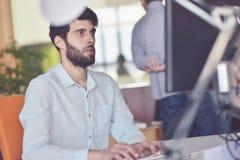 研究台式计算机的年轻商人在他的在现代明亮的起始的办公室内部的书桌 库存图片