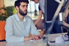 研究台式计算机的年轻商人在他的在现代明亮的起始的办公室内部的书桌 免版税库存图片