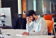研究台式计算机的年轻商人在他的在现代明亮的起始的办公室内部的书桌 免版税库存照片