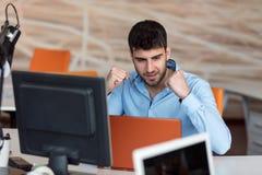 研究台式计算机的愉快的年轻商人在他的在现代明亮的起始的办公室内部的书桌 免版税图库摄影