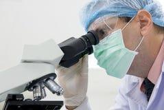 研究员与显微镜一起使用 免版税库存照片