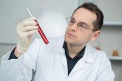 研究员在工作在有血液吸移管的实验室 库存图片