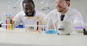 研究员In Laboratory,男性Scietists医生队谈论试管,当女性专家使用时 股票录像