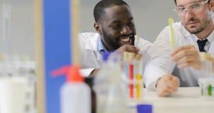 研究员In Laboratory,男性Scietists医生队谈论试管,当女性专家使用时 影视素材
