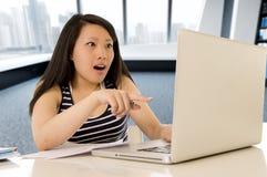 研究和学习她的计算机的愉快的中国亚裔妇女坐在现代办公桌微笑快乐 免版税图库摄影