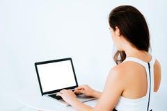 研究和键入在书桌上的膝上型计算机的年轻可爱的白种人女商人-有在显示器屏幕上的空的拷贝空间的在膝上型计算机 库存照片