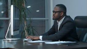 研究和键入膝上型计算机的英俊的美国黑人的商人在办公室 库存图片