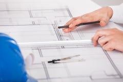 研究图纸设计的建筑师 免版税库存照片
