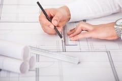 研究图纸设计的建筑师 免版税库存图片
