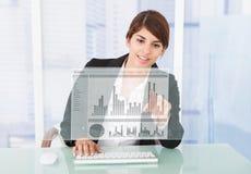 研究图表的愉快的女实业家在计算机书桌 免版税库存照片
