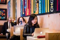 研究在一个咖啡馆的计算机的人们在格林尼治村, NYC 免版税库存图片