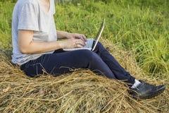 研究在一个干草堆的一台膝上型计算机的女孩在乡下 库存照片
