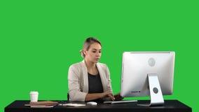 研究在一个绿色屏幕上的计算机,色度钥匙的美丽的白肤金发的妇女 影视素材