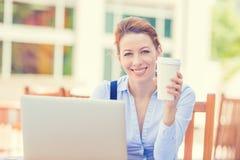 研究在公司办公室饮用的咖啡之外的膝上型计算机的微笑的妇女 免版税图库摄影