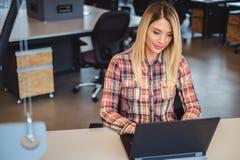 研究在办公室和微笑的一台膝上型计算机的妇女 库存图片