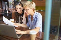 研究在咖啡店的膝上型计算机的两名女实业家 库存照片