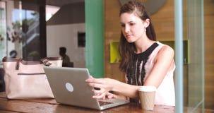 研究在咖啡店的膝上型计算机的年轻女实业家 股票录像