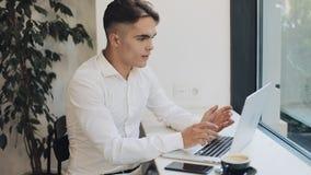 研究在咖啡馆的手提电脑的英俊的年轻商人 愉快知道的好的消息激动和 遥远做自由职业者 股票视频
