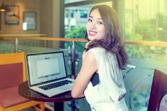 研究在咖啡馆的膝上型计算机的一个美丽的中国女孩 免版税库存照片