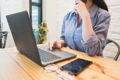 研究在咖啡馆的膝上型计算机的少妇 职业妇女概念 免版税库存照片