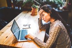 研究在咖啡馆里面的便携式计算机的毛线衣的美丽的年轻深色的女孩在木桌上在窗口附近 冬天和圣诞节 图库摄影