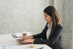 研究在她的wor的膝上型计算机的美丽的亚裔年轻女实业家 免版税库存图片