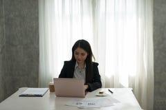 研究在她的wor的膝上型计算机的美丽的亚裔年轻女实业家 库存照片