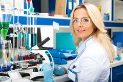 研究在实验室里的年轻可爱的妇女科学家 库存照片